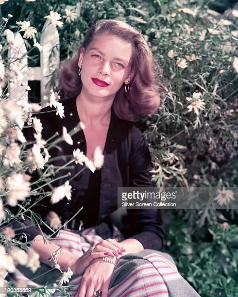 Lauren Bacall US actress wearing a black jacket and top with a skirt with horizontal stripes posing in a garden beside a display of daisies circa 1950