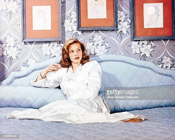 Lauren Bacall US actress wearing a long white dressing gown while reclining on a bed with three pictures hanging on the wall behind her circa 1950