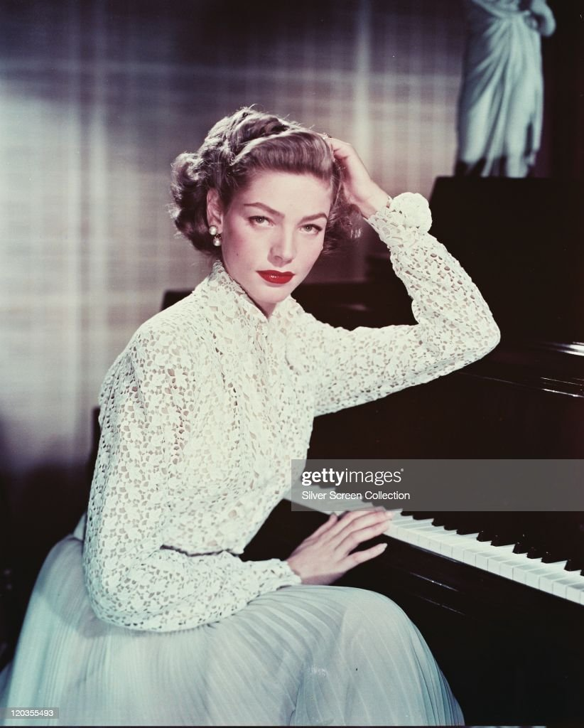 Lauren Bacall US actress wearing a white macrame blouse and a light blue skirt while posing beside a piano with one hand on the keys circa 1955