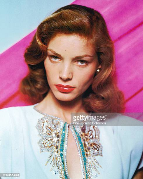 Lauren Bacall US actress wearing a white top with a keyhole necklace with sequinned decoration in a studio portrait against a pink background circa...