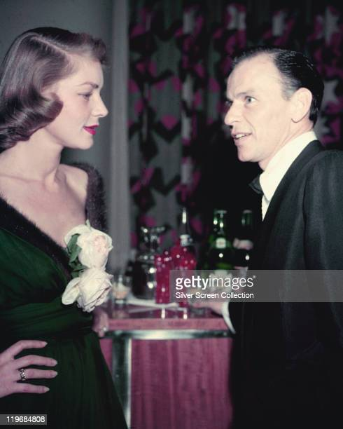 Lauren Bacalll US actress in conversation with Frank Sinatra US singer and actor at a bar circa 1955
