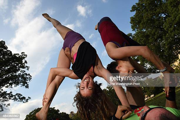 Lauren Danella center Lindsey Fong right and Brian Cruikshank bottom right take part in acroyoga at Meridian Hill Park on Sunday August 09 2015 in...