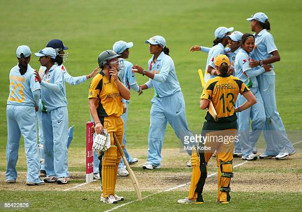 Lauren Ebsary and Rene Farrell of Australia stand dejected as the Indian players celebrate their win during the ICC Women's World Cup 2009 Super Six...