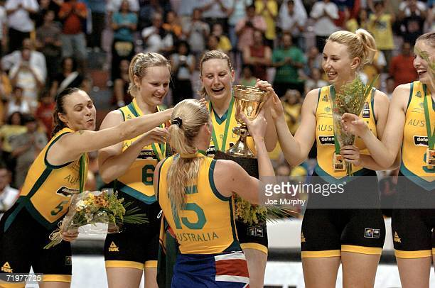 Lauren Jackson of Australia holds up the gold cup for her teammates on the medal stand after the gold medal game between Australia and Russia during...