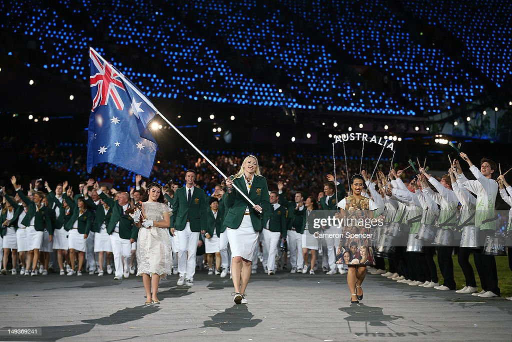 Lauren Jackson of the Australian Olympic basketball team carries her country's flag as she leads the Australian team into the stadium during the...