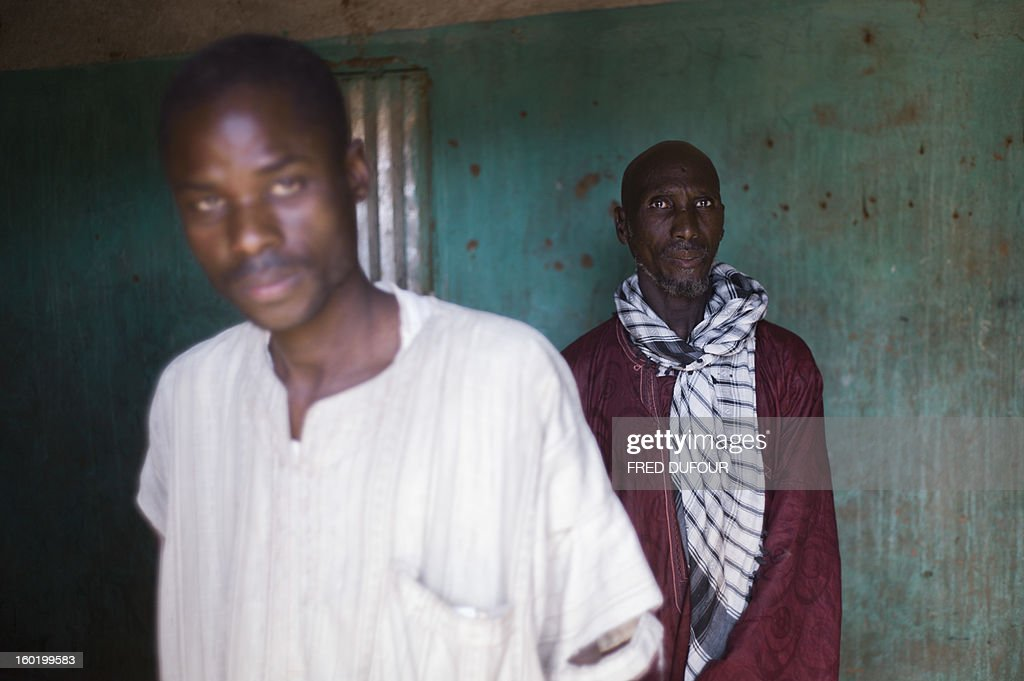 Laurence BOUTREUX - Idrissa Maiga (R), a Malian farmer, poses with one of his sons in his house in Konna on January 27, 2013. Maiga's second wife, 41, and two boys and a girl aged from 10 to 14 reportedly perished on the morning of the 11 January during a French army air raid and were buried the same afternoon.