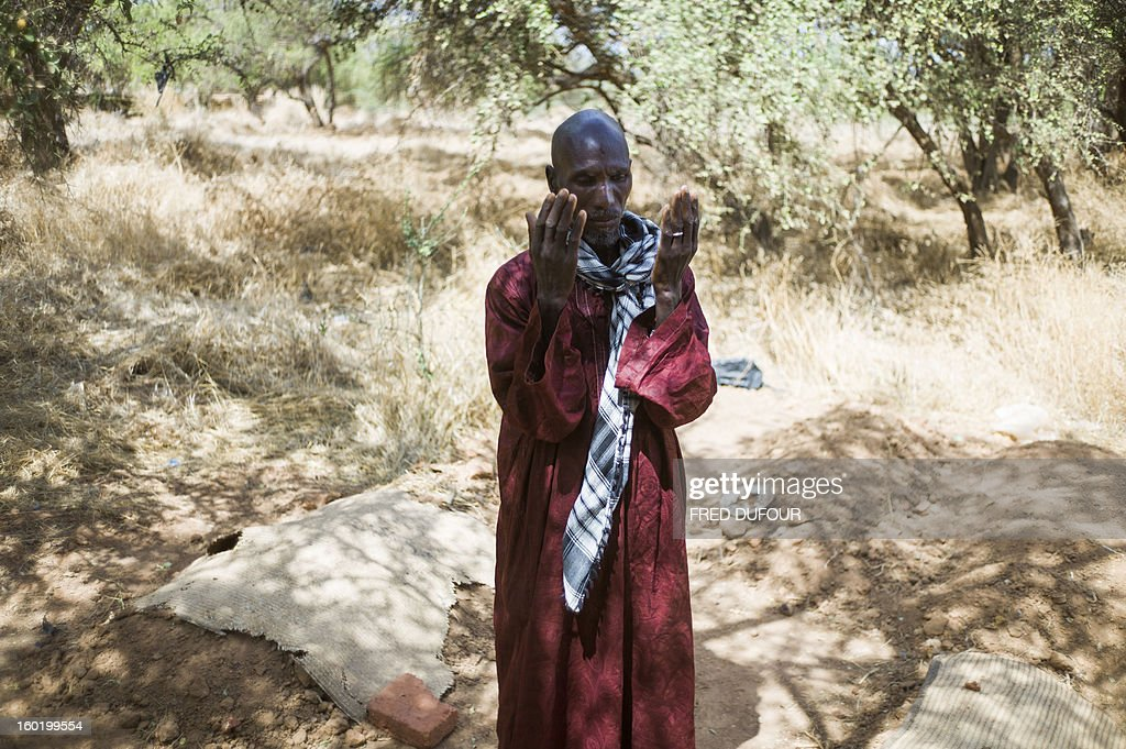 Laurence BOUTREUX - Idrissa Maiga, a Malian farmer, prays among the graves of his wife and three of his children in a cemetery behind the Konna school on January 27, 2013 who were reportedly killed by French army air strikes on January 11. Maiga's second wife, 41, and two boys and a girl aged from 10 to 14 allegedly perished on the morning of the 11th during the air raid and were buried the same afternoon. AFP PHOTO / FRED DUFOUR