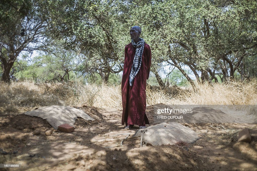 Laurence BOUTREUX - Idrissa Maiga, a Malian farmer, stands among the graves of his wife and three of his children in a cemetery behind the Konna school on January 27, 2013 who were reportedly killed by French army air strikes on January 11. Maiga's second wife, 41, and two boys and a girl aged from 10 to 14 allegedly perished on the morning of the 11th during the air raid and were buried the same afternoon.