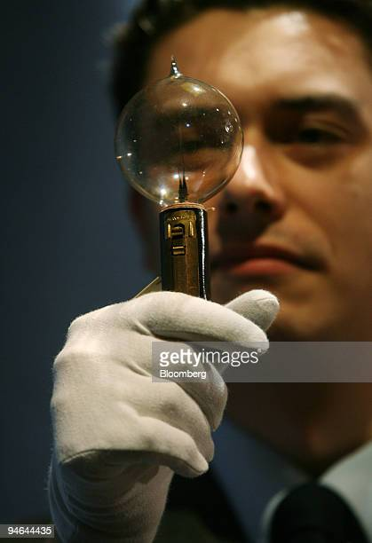Laurence Fisher a specialist in mechanical music at Christie's holds one of 23 original light bulbs which was used as evidence in the 1890 trial...