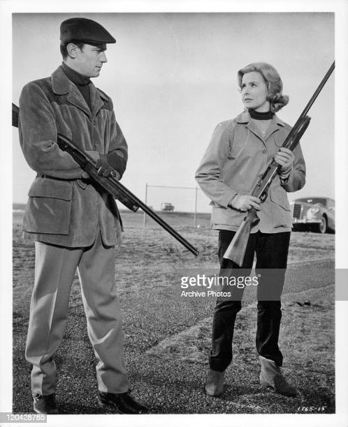Laurence Harvey and Dina Merrill standing with guns in a scene from the film 'Butterfield 8' 1960