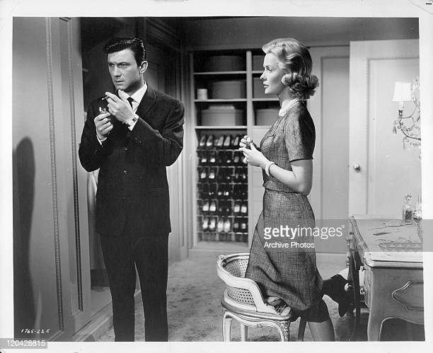 Laurence Harvey with cigarette while Dina Merrill stands in a scene from the film 'Butterfield 8' 1960