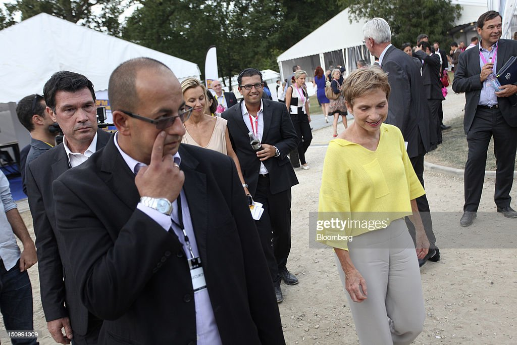 Laurence Parisot president of the Mouvement des Enterprises de France right walks through the university grounds during the Medef conference at the...