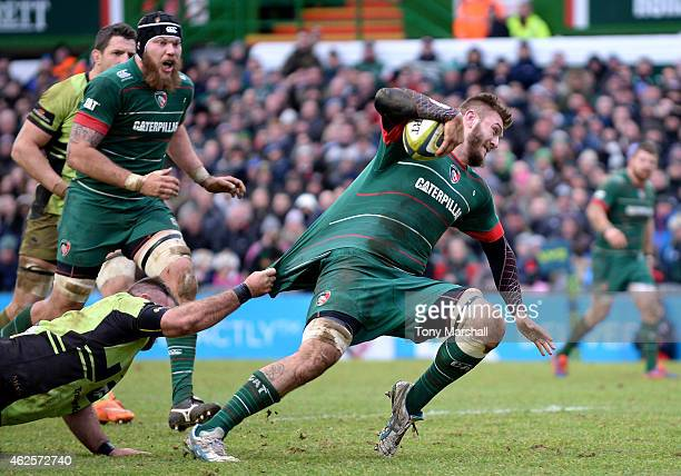 Laurence Pearce of Leicester Tigers charges for the try line to score their second try as Gareth Denman of Northampton Saints gabs his shirt during...