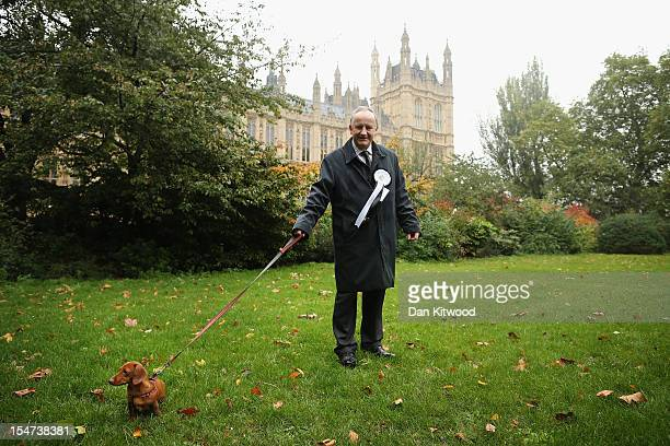 Laurence Robertson Conservative MP for Tewkesbury stands in front of The Houses of Parliament with his dog Sausage a Miniature Dachshund during the...