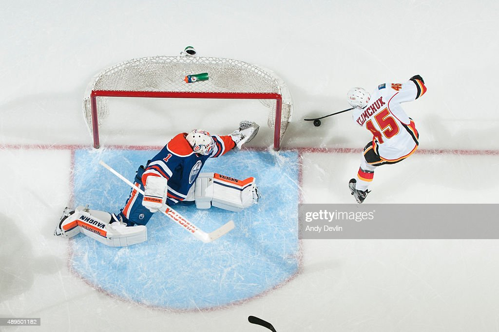 Laurent Brossoit #1 of the Edmonton Oilers dives to cover the net as Morgan Klimchuk #45 of the Calgary Flames plays the puck beside the net on September 21, 2015 at Rexall Place in Edmonton, Alberta, Canada.