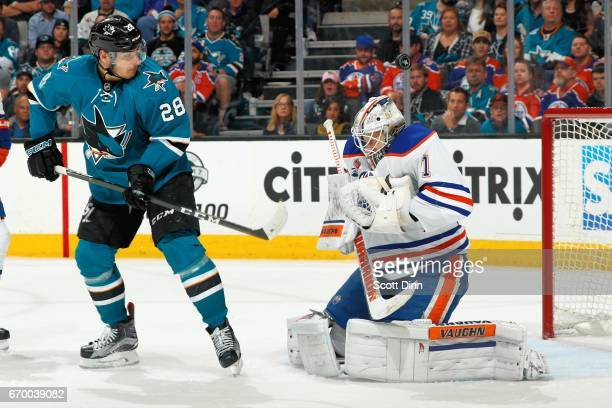 Laurent Brossoit of the Edmonton Oilers makes a save as Timo Meier of the San Jose Sharks looks in Game Four of the Western Conference First Round...