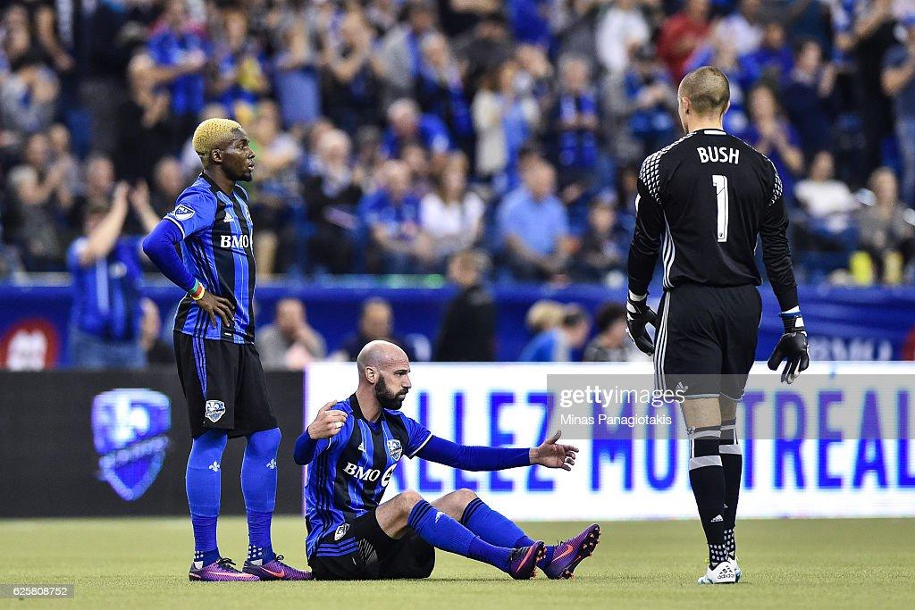 Laurent Ciman #23 of the Montreal Impact reacts as he sits on the pitch while teammates Ambroise Oyongo #2 and Evan Bush #1 walk towards him during leg one of the MLS Eastern Conference finals against the Toronto FC at Olympic Stadium on November 22, 2016 in Montreal, Quebec, Canada. The Montreal Impact defeated the Toronto FC