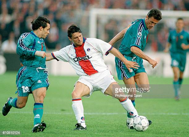 Laurent Fournier of Paris SaintGermain is challenged by Barcelona defenders Sergi Barjuan and Gheorghe Popescu during the UEFA European Cup Winner's...