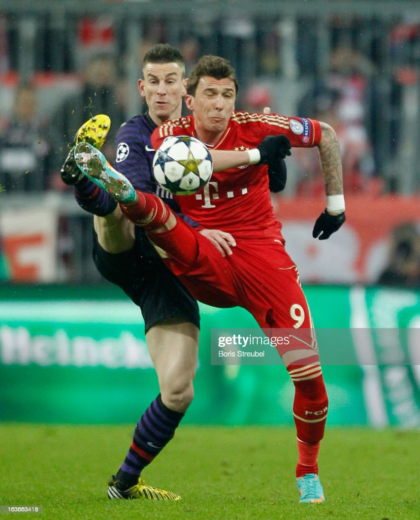 Laurent Kocielny (L) of Arsenal challenges <a gi-track='captionPersonalityLinkClicked' href=/galleries/search?phrase=Mario+Mandzukic&family=editorial&specificpeople=4476149 ng-click='$event.stopPropagation()'>Mario Mandzukic</a> of Bayern Munich during the UEFA Champions League Round of 16 second leg match between Bayern Muenchen and Arsenal FC at Allianz Arena on March 13, 2013 in Munich, Germany.