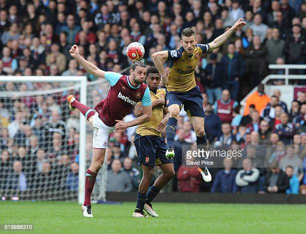 Laurent Koscielny and Alex Iwobi of Arsenal challenged Andy Carroll of West Ham during the Barclays Premier League match between West Ham United and...