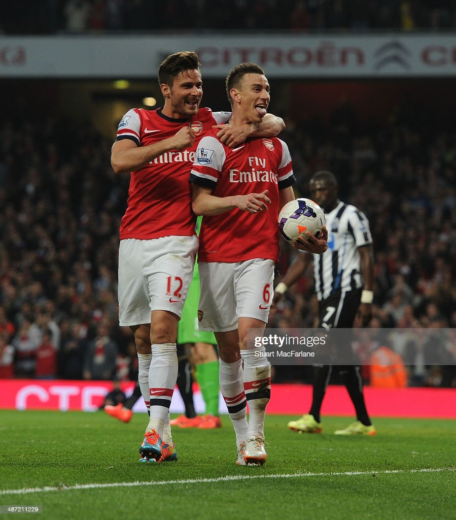 Laurent Koscielny celebrates scoring Arsenal's goal with (R) Olivier Giroud during the Barclays Premier League match between Arsenal and Newcastle United at Emirates Stadium on April 28, 2014 in London, England.