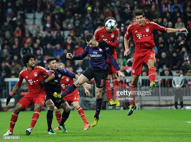 Laurent Koscielny heads Arsenal's 2nd goal as he gets between Mario Gomez and Javier Martinez of Bayern during the UEFA Champions League Round of 16...