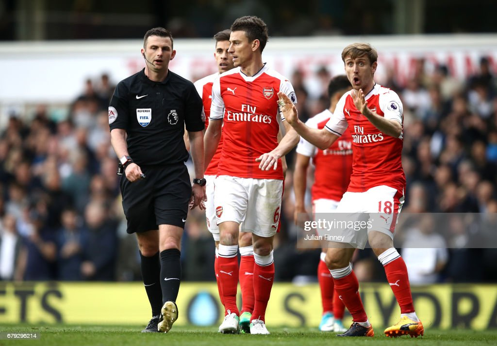 Laurent Koscielny of Arsenal and Nacho Monreal of Arsenal plead with referee Michael Oliver after he awards Tottenham Hotspur a penalty during the Premier League match between Tottenham Hotspur and Arsenal at White Hart Lane on April 30, 2017 in London, England.