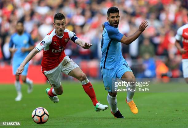 Laurent Koscielny of Arsenal and Sergio Aguero of Manchester City compete for the ball during the Emirates FA Cup SemiFinal match between Arsenal and...