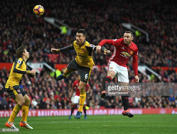 Laurent Koscielny of Arsenal and Wayne Rooney of Manchester United battle for possession in the air during the Premier League match between...