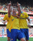Laurent Koscielny of Arsenal celebrates scoring his team's second goal with Olivier Giroud and Per Mertesacker during the Emirates Cup match between...