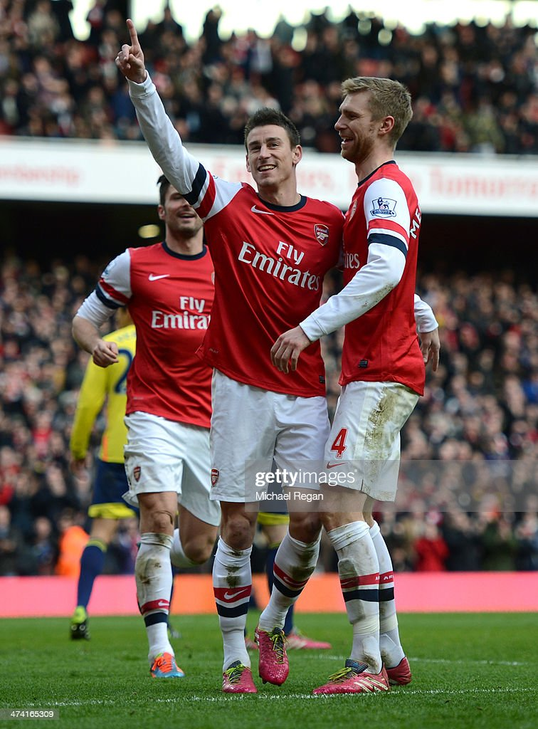 Laurent Koscielny of Arsenal (C) celebrates with team-mates Olivier Giroud of Arsenal (L) and Per Mertesacker of Arsenal after scoring their third goal during the Barclays Premier League match between Arsenal and Sunderland at Emirates Stadium on February 22, 2014 in London, England.