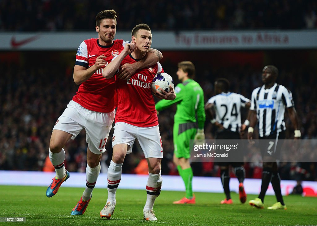 <a gi-track='captionPersonalityLinkClicked' href=/galleries/search?phrase=Laurent+Koscielny&family=editorial&specificpeople=2637418 ng-click='$event.stopPropagation()'>Laurent Koscielny</a> of Arsenal celebrates wth <a gi-track='captionPersonalityLinkClicked' href=/galleries/search?phrase=Olivier+Giroud&family=editorial&specificpeople=5678034 ng-click='$event.stopPropagation()'>Olivier Giroud</a> (L) as he scores their first goal during the Barclays Premier League match between Arsenal and Newcastle United at Emirates Stadium on April 28, 2014 in London, England.