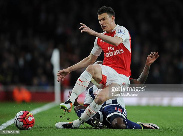 Laurent Koscielny of Arsenal challenged by Saido Berahino of WBA during the Barclays Premier League match between Arsenal and West Bromwich Albion at...