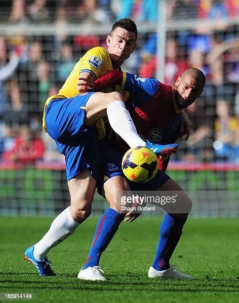 Laurent Koscielny of Arsenal challenges Adlene Guedioura of Crystal Palace during the Barclays Premier League match between Crystal Palace and...