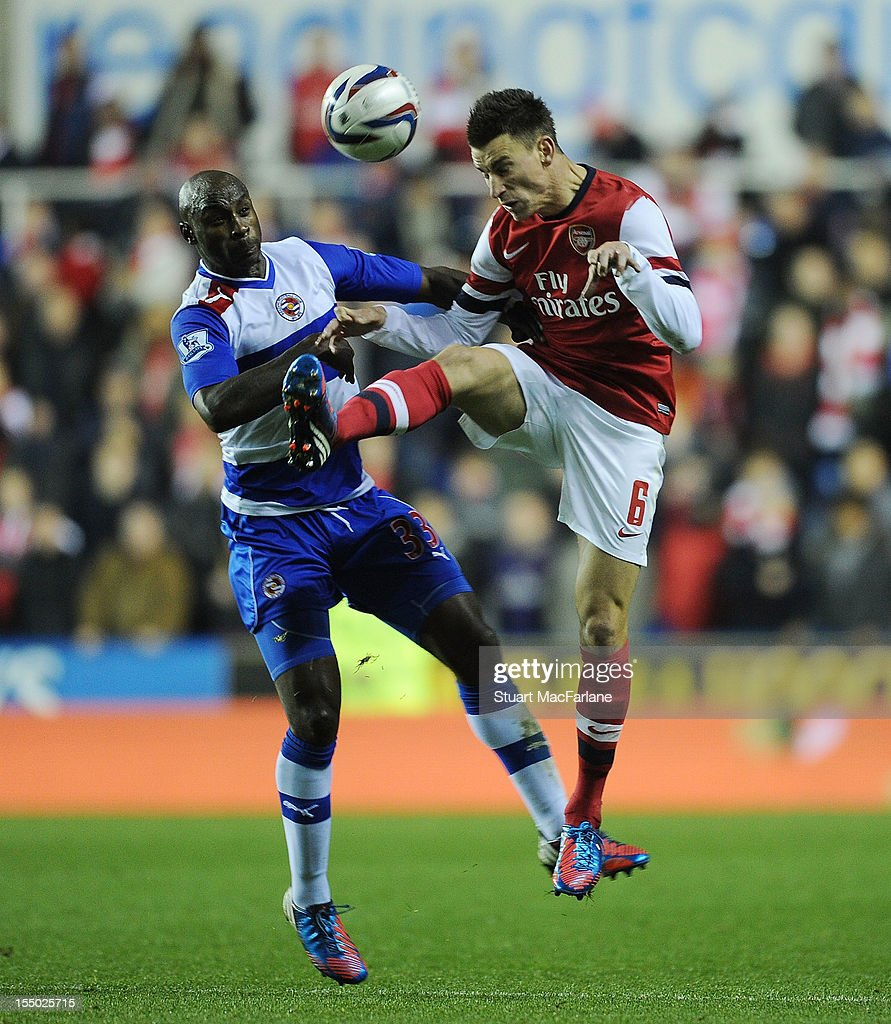 Laurent Koscielny of Arsenal challenges Jason Roberts of Reading during the Capital One Cup match between Arsenal and Reading at Madejski Stadium on October 30, 2012 in Reading, England.