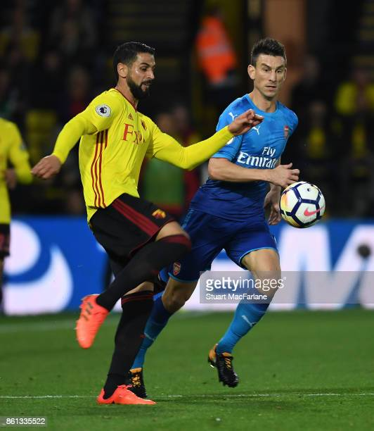 Laurent Koscielny of Arsenal challenges Miquel Britos of Watford during the Premier League match between Watford and Arsenal at Vicarage Road on...