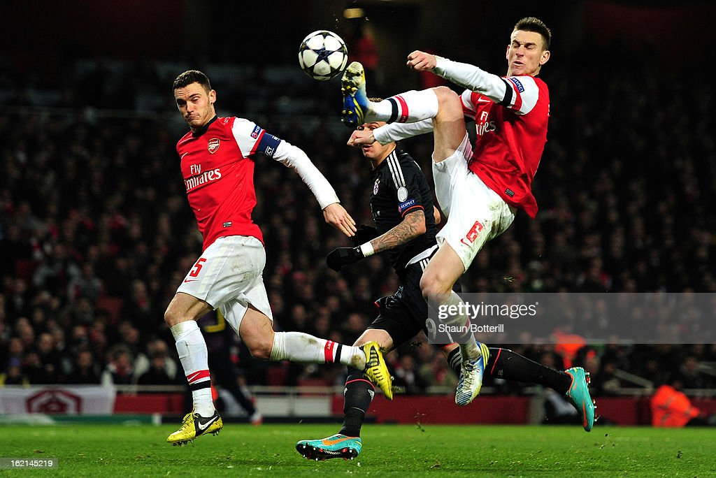Laurent Koscielny of Arsenal clears the ball in front of Mario Mandzukic of Bayern Muenchen and his team-mate Thomas Vermaelen during the UEFA Champions League round of 16 first leg match between Arsenal and Bayern Muenchen at Emirates Stadium on February 19, 2013 in London, England.