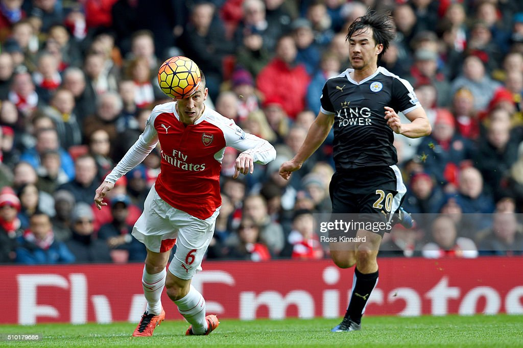Laurent Koscielny of Arsenal heads the ball back to Petr Cech under pressure from Shinji Okazaki of Leicester City during the Barclays Premier League match between Arsenal and Leicester City at Emirates Stadium on February 14, 2016 in London, England.