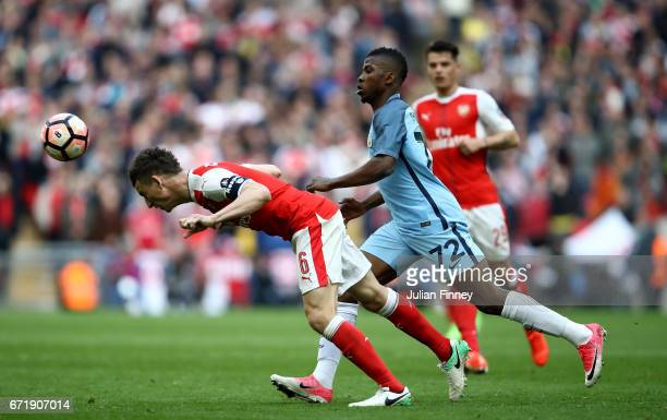 Laurent Koscielny of Arsenal heads the ball in front of Kelechi Iheanacho of Manchester City during the Emirates FA Cup SemiFinal match between...