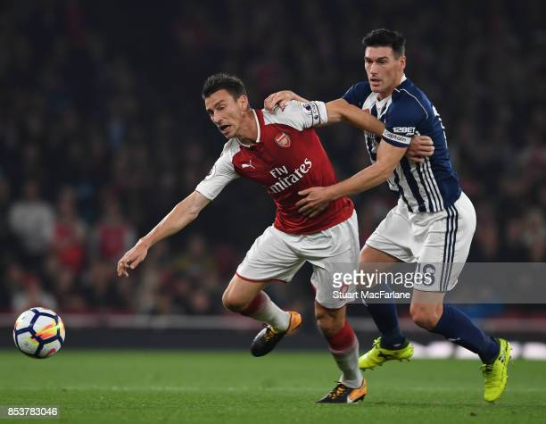 Laurent Koscielny of Arsenal is challenged by Gareth Barry of WBA during the Premier League match between Arsenal and West Bromwich Albion at...