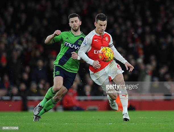 Laurent Koscielny of Arsenal is challenged by Shane Long of Southampton during the Barclays Premier League match between Arsenal and Southampton at...