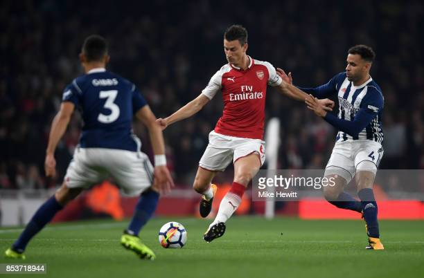 Laurent Koscielny of Arsenal is faced by Hal RobsonKanu and Kieran Gibbs of West Bromwich Albion during the Premier League match between Arsenal and...