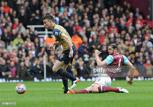 Laurent koscielny of Arsenal is fouled by Andy Carroll of West Ham during the Barclays Premier League match between West Ham United and Arsenal at...