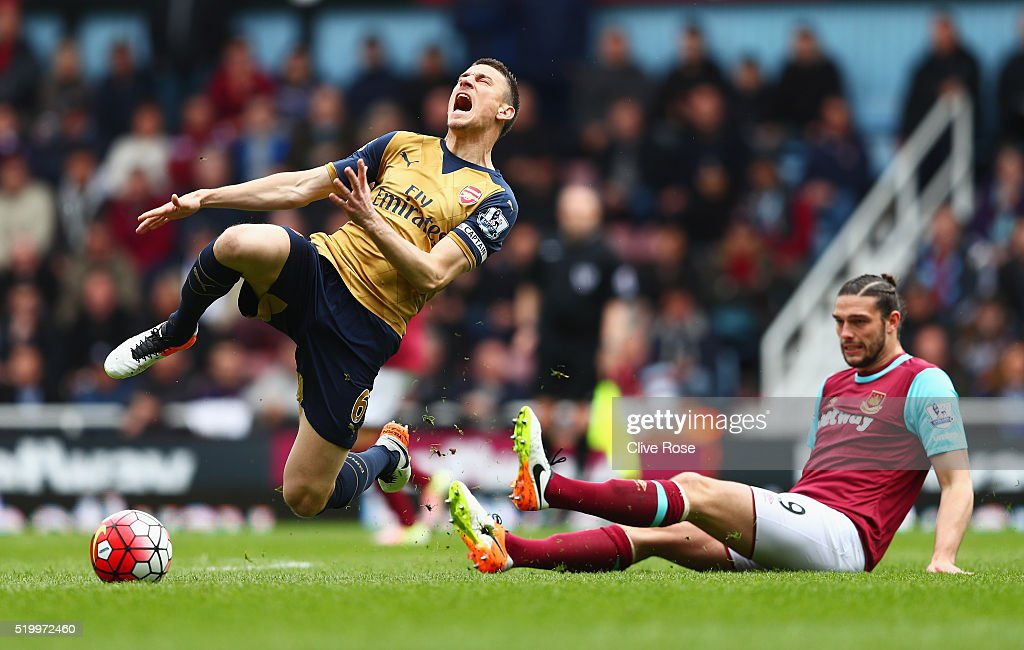 <a gi-track='captionPersonalityLinkClicked' href=/galleries/search?phrase=Laurent+Koscielny&family=editorial&specificpeople=2637418 ng-click='$event.stopPropagation()'>Laurent Koscielny</a> of Arsenal is tackled by <a gi-track='captionPersonalityLinkClicked' href=/galleries/search?phrase=Andy+Carroll+-+Soccer+Player&family=editorial&specificpeople=1449090 ng-click='$event.stopPropagation()'>Andy Carroll</a> of West Ham United during the Barclays Premier League match between West Ham United and Arsenal at the Boleyn Ground on April 9, 2016 in London, England.