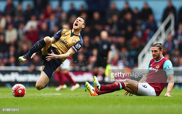 Laurent Koscielny of Arsenal is tackled by Andy Carroll of West Ham United during the Barclays Premier League match between West Ham United and...