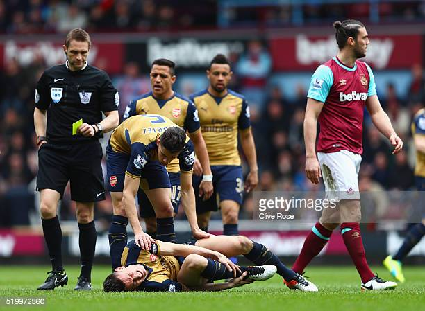 Laurent Koscielny of Arsenal lies injured after being tackled while refereee Craig Pawson prepares for an yellow card to Andy Carroll of West Ham...