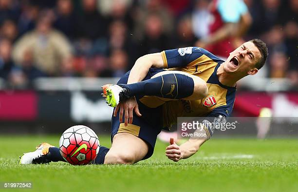 Laurent Koscielny of Arsenal reacts after being tackled by Andy Carroll of West Ham United during the Barclays Premier League match between West Ham...