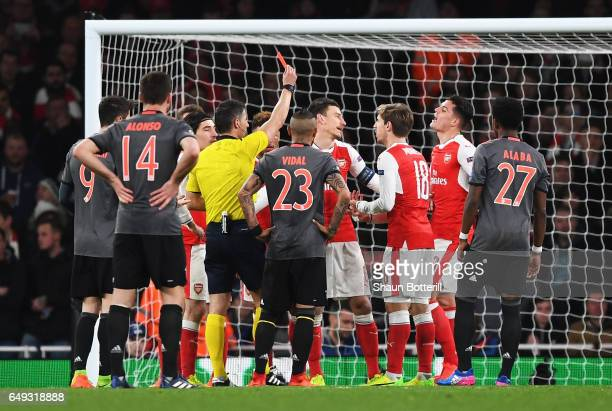 Laurent Koscielny of Arsenal reacts as he is shown a red card by referee Anastasios Sidiropoulos and is sent off during the UEFA Champions League...
