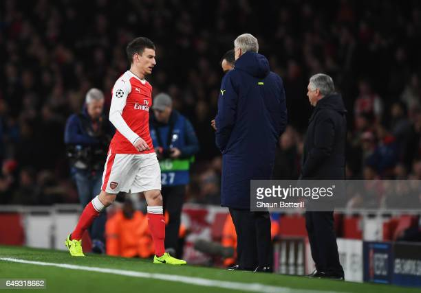 Laurent Koscielny of Arsenal walks past Arsene Wenger Manager of Arsenal as he is sent off during the UEFA Champions League Round of 16 second leg...