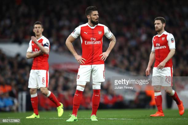 Laurent Koscielny Olivier Giroud and Shkodran Mustafi of Arsenal look on during The Emirates FA Cup QuarterFinal match between Arsenal and Lincoln...